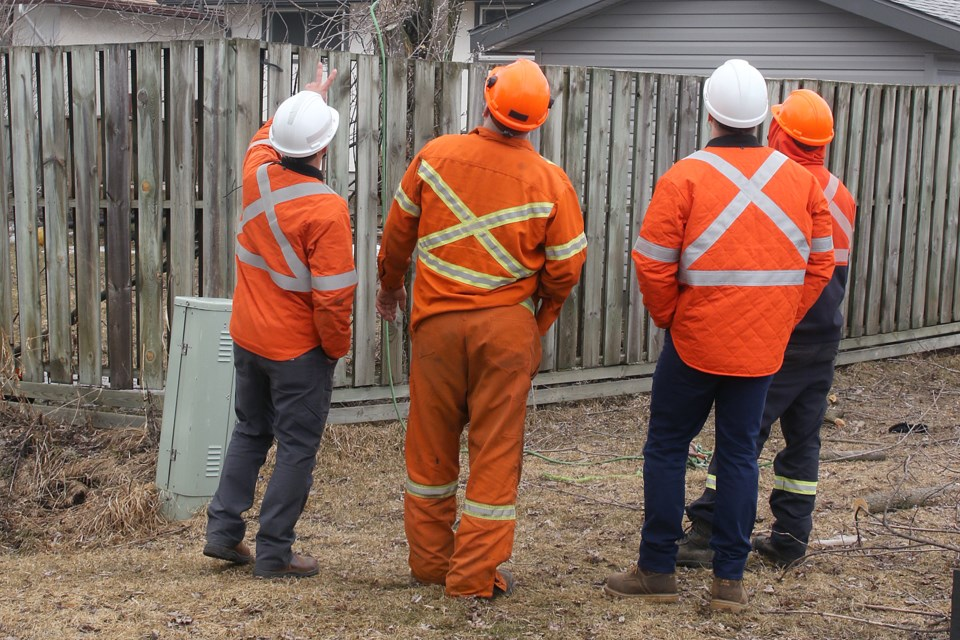 Synergy North workers discuss an electrocution that took place on Kensington Drive on Monday, April 8, 2019. (Leith Dunick, tbnewswatch.com)