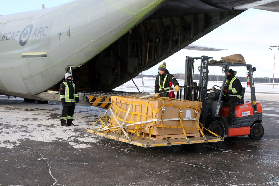 Workers unload crates of toys from a Royal Canadian Airforce Hercules plane. The toys will be distributed to a pair of remote, fly-in communities in Ontario's north. (Leith Dunick, tbnewswatch.com)