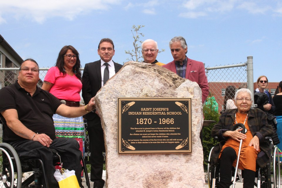Phillip Pelletier (left), Ann magiskan, Pino Tassone, Deacon Armand Danis, Bill Mauro, and Dolores Wawia in front of the monument. (Michael Charlebois, tbnewswatch)