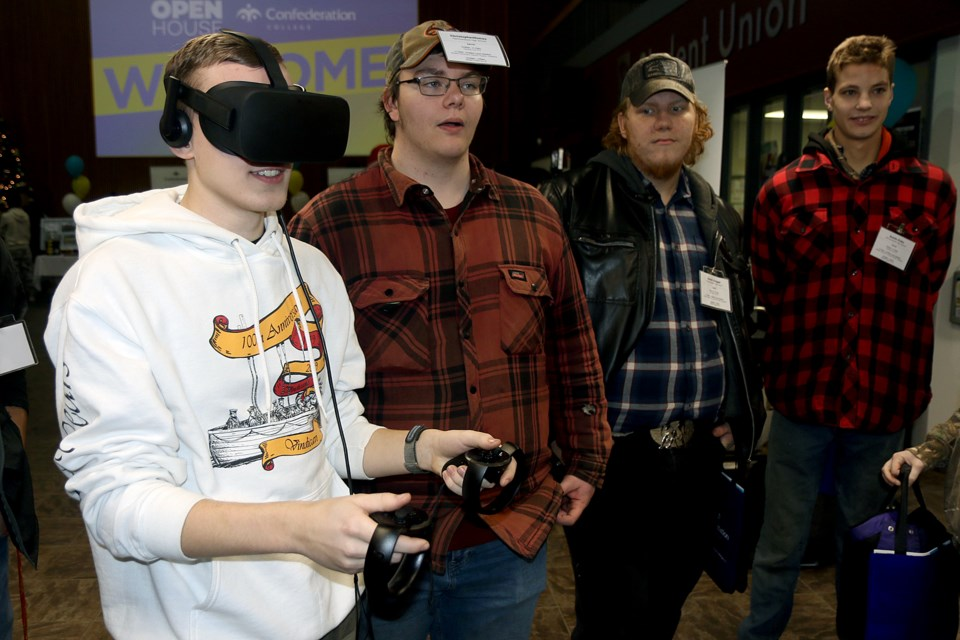 Evan Strilchuk (left) tests out virtual reality equipment during Confederation College's annual recruitment day. (Leith Dunick, tbnewswatch.com)