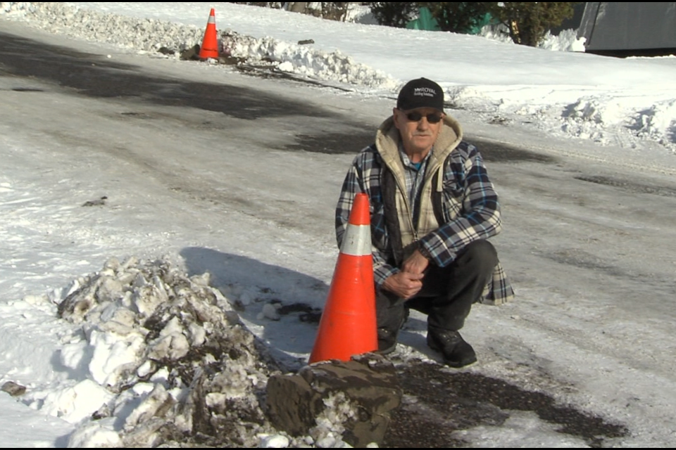 Don Williams crouches beside one of the curbstones dug up by a grader clearing his street (Jon Wilson/TBTV photo)