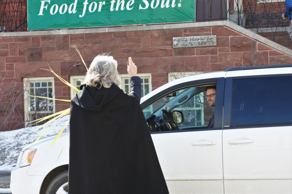 "Deborah Kraft, rector at St. Paul's Anglican Church, offered ""drive-by"" blessings to congregants on Palm Sunday."