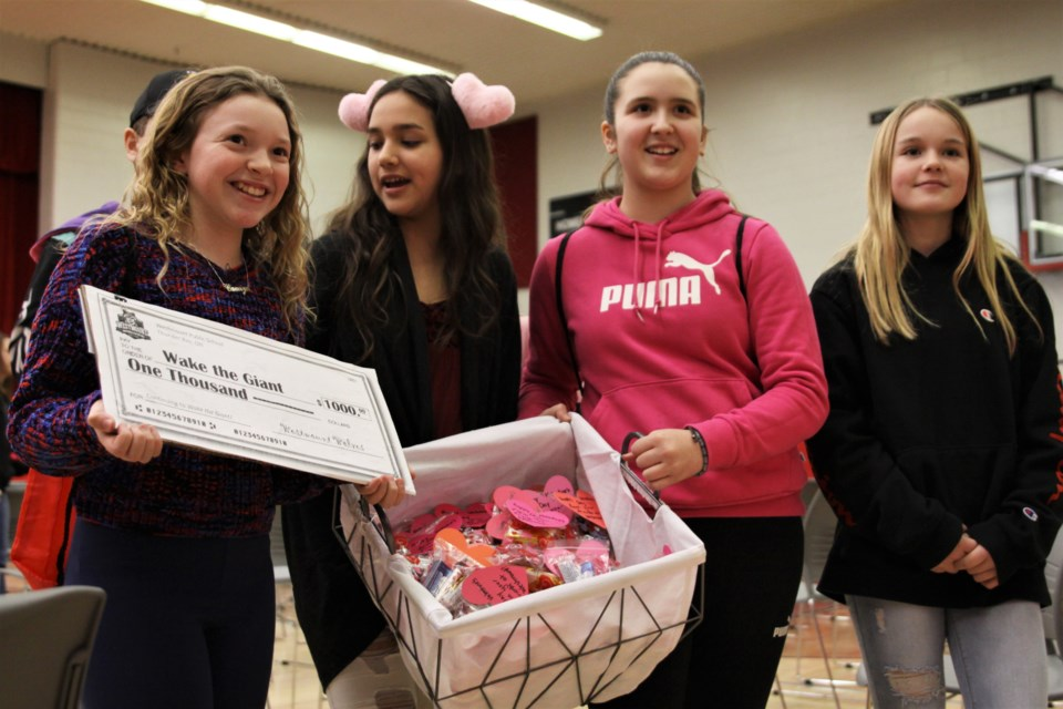Westmount students (from left) Camryn Pereira, Jolie Whitecrow, Jersey Daniels-Wakefield, and Tykara Balke-Brewer deliver candygrams, along with a $1,000 cheque for Wake the Giant, at DFC Friday. (Photos by Ian Kaufman, tbnewswatch.com)