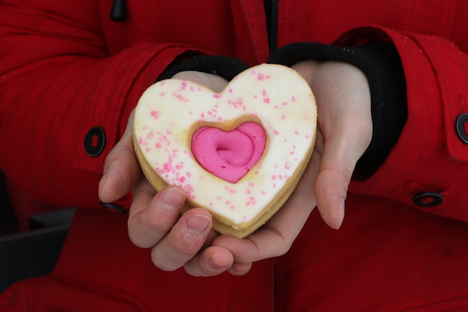Shannon Hobbs holds a heart-shaped cookie on Thursday, Feb. 18, 2021, outside of Bay Village Coffee, which is selling the treats to raise money for the Thunder Bay Regional Health Sciences Foundation's Our Hearts at Home cardiovascular surgery campaign. (Leith Dunick, tbnewswatch.com)