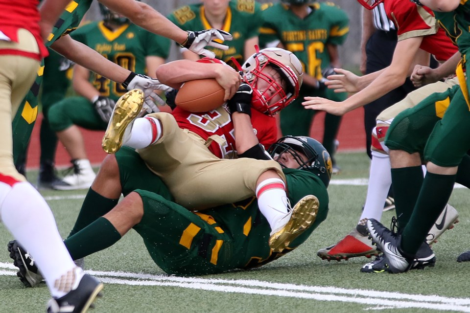 Hammarskjold's Dylan Halls is hauled down by a pair of St. Patrick defenders on Thursday, Sept. 19, 2019 at Fort William Stadium. (Leith Dunick, tbnewswatch.com)
