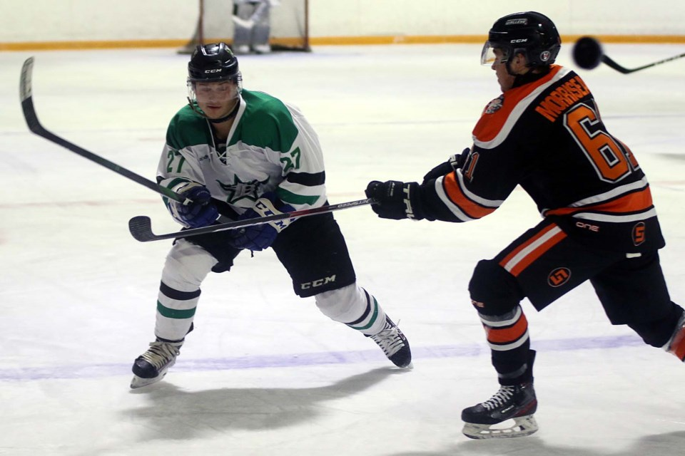 Thunder Bay's Michael Stubbs (left) flips the puck past Kam River's Trenton Morriseau on Friday, Nov. 13 at the Norwest Arena. (Leith Dunick, tbnewswatch.com)