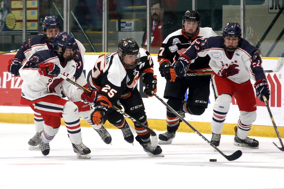 Magog's Justin Robidas (25) tries to break free against a trio of Tisdale Trojans in semifinal play at the TELUS Cup on Saturday, April 27, 2019 at Fort William Gardens. (Leith Dunick, tbnewswatch.com)