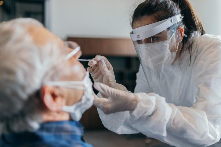 old man getting nasal swab from female medical worker in ppe