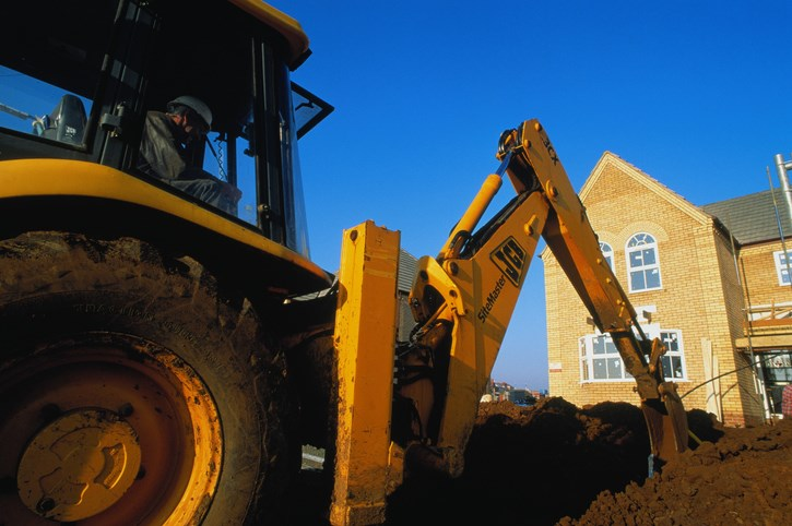 excavator digging outside house