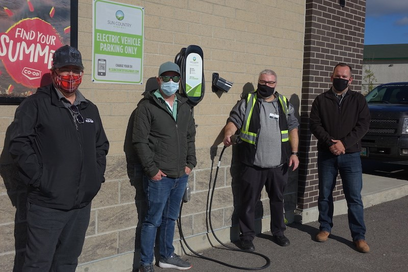 Thompson Co-op Gas Bar  board member Les Ellsworth, board president Rob Ellsworth, general manager Alvaro Filipe and board member Mike Lawson pose by the gas station's new level 2 electric vehicle charging station.
