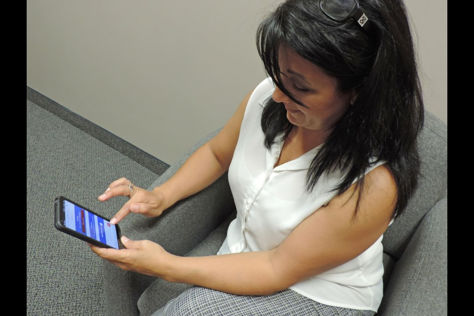 Heart Innovation Research Program participant and heart attack survivor Grace Cabral demonstrates use of the online Prodromal Symptoms Screening Scale on her phone. Supplied photo