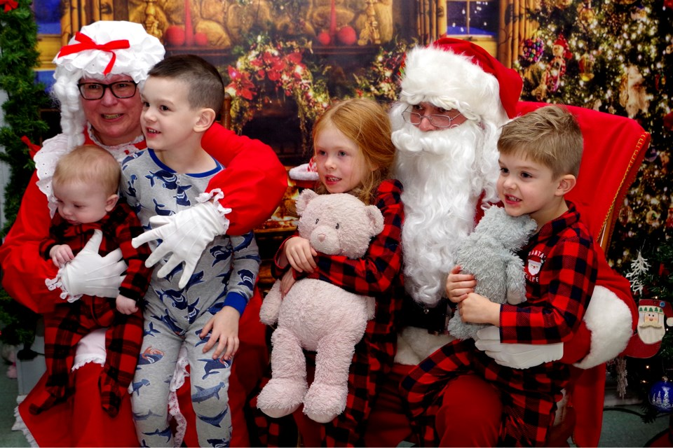 Baby William, Mason , Emma, and Andrew Quinn snuggled up with Santa and Mrs. Claus at the Port Robinson kids' Christmas party Friday night. Bob Liddycoat / Thorold News