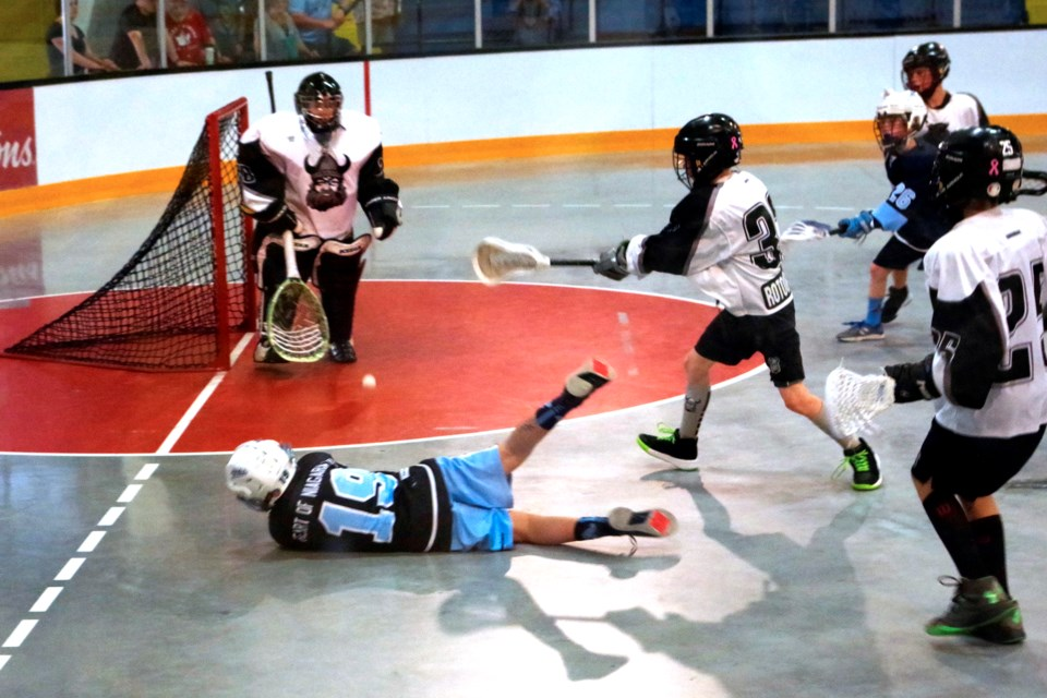 Now that's focus: Belal Hamdani #19 fires a shot while being knocked to the floor during Peewee lacrosse final game. St. Catharines beat Awkesasne to win the division. Bob Liddycoat / Thorold News