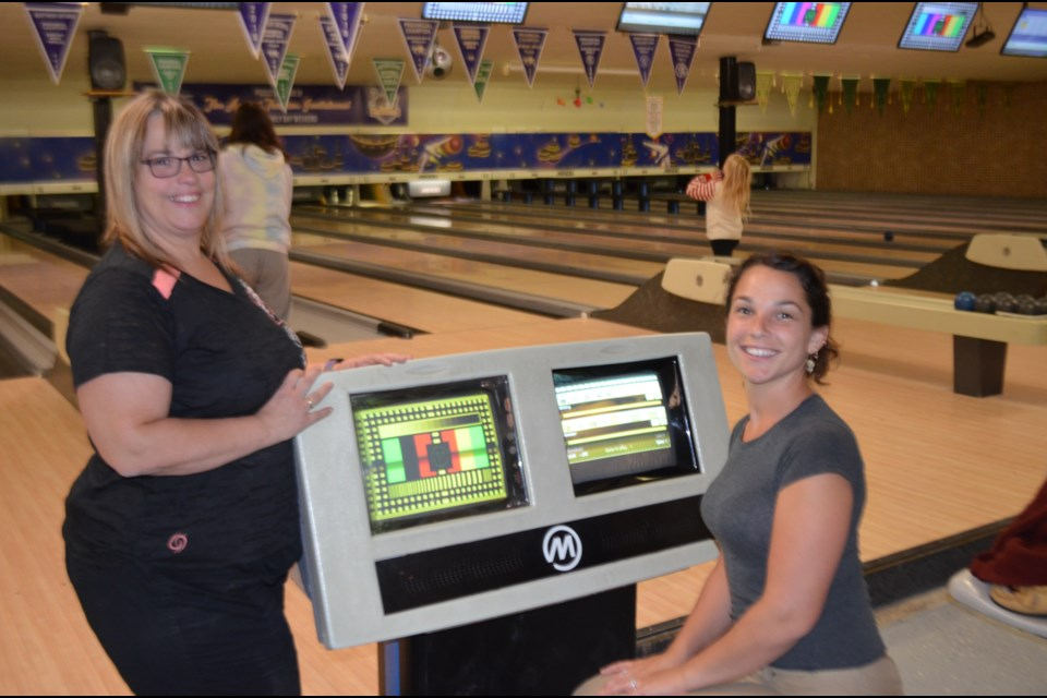 Mid-Town Bowl owner Natalie Berry, left, discusses the game with bowler Nikky Bouillon. Berry has owned the family business for 25 years. Wayne Snider for TimminsToday