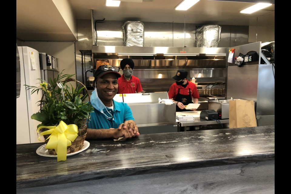 Siva Mylvaganam is behind the counter in front of the open kitchen at New Burger Planet Inc. The new restaurant features a unique fresh take on old favourites. Wayne Snider for TimminsToday