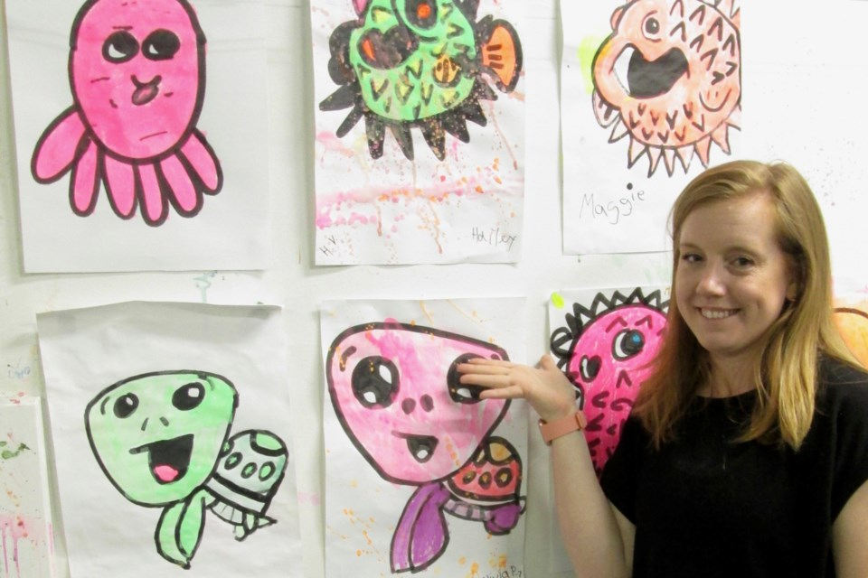 Alicia Pirie, owner of Art and Soul in the Porcupine Mall, shows some of the glow-in-the-dark artwork created by her young clients. Wayne Snider for TimminsToday