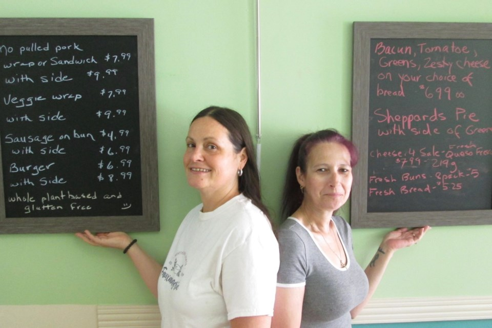 Rocsi Carr, left, and Danielle Moreau display the menu boards at Northern Lights Fauxmagerie. The two friends recently opened the Downtown Timmins restaurant, which serves a variety of flavourful plant-based meals and snacks. Wayne Snider for TimminsToday