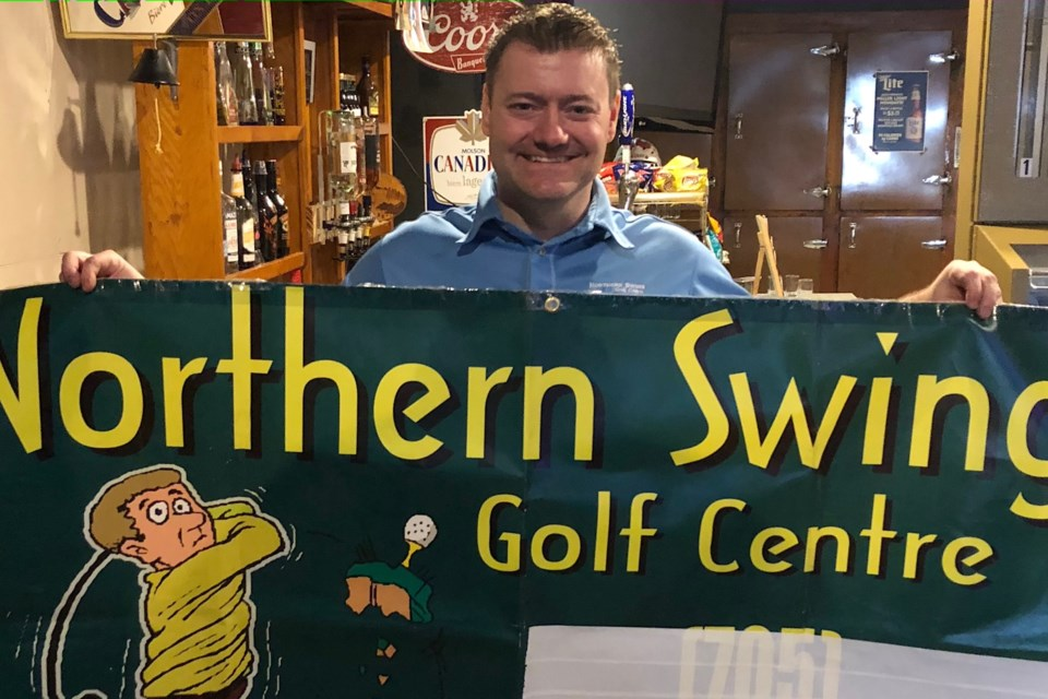 Mat Vachon, owner of Northern Swing, displays a sign for his business. Vachon has moved his golf simulation, which allows golfers to play indoors, into Jake's Bar and Grill in South Porcupine. Wayne Snider for TimminsToday