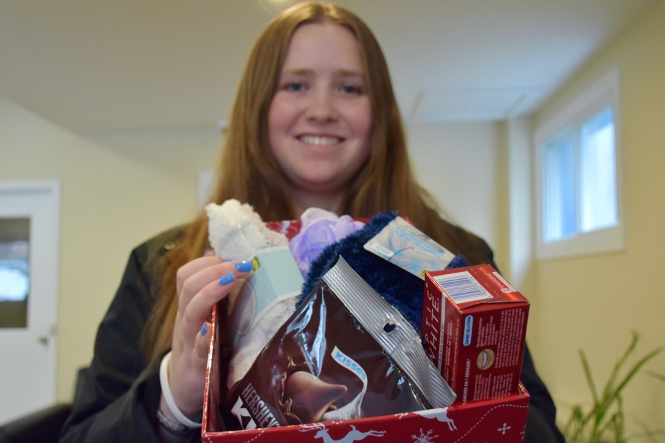 Megan Rowe with one of the shoeboxes that will be given to Living Space users this Christmas. The community is invited to donate boxes until Dec. 20. Maija Hoggett/TimminsToday
