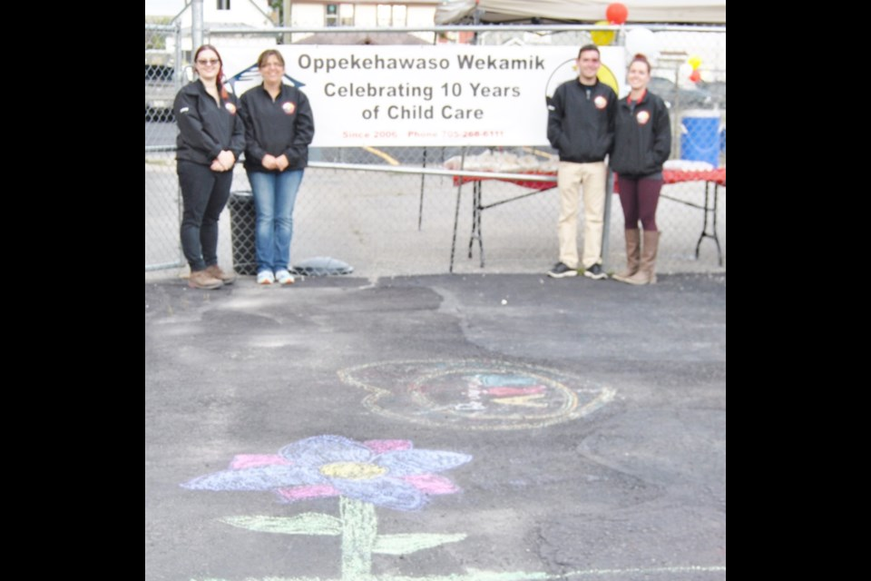 Staff of Oppekehawso Wekamin Daycare display chalk art celebrating 10th anniversary of the daycare. From left to right: Stacy Naywroski, manager; Janice Duhn, Nic Gauthier and Melissa Beamish. Photo: Frank Giorno, Timminstoday.com