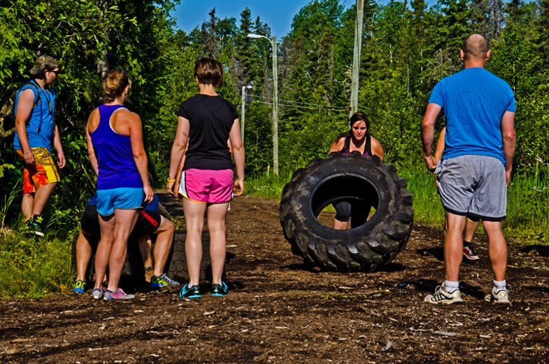 Nancy Demers and her team flip tires to successfully make their way through the first obstacle, Tenacious Ten.