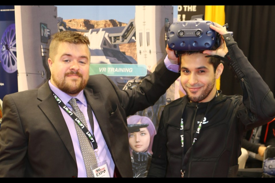 Next Frontier Corp. CEO Jason Michaud of Cochrane, left, was with technology officer Jawad El Houssine to demonstrate a virtual reality headset along with a virtual reality bodysuit. Both men were at the Big Event Mining Expo held in Timmins in June