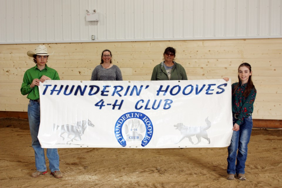 The Thunderin' Hooves 4-H club will be one of the many user groups from around the Athabasca region that will make good use of the Ag Society's new multi-use facility. The fundraising for the building is still underway with the $20,000 first place cash prize up for grabs with the purchase of a $20 ticket that can be found at businesses throughout town. Pictured: Ty and Isabelle Tremblay hold their club banner inside the new facility, with Ag Society director Katherine Tremblay and treasurer Dee Lambert keeping their distance behind the banner.