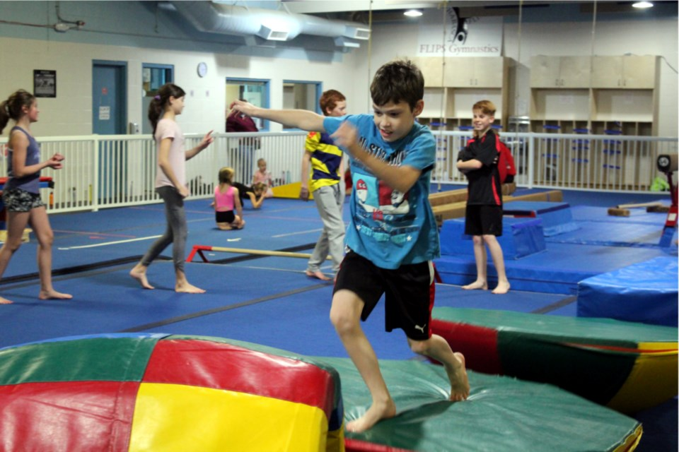 Rexson Turner ran the course at FLIPS Gymnastics Club Nov. 5 in the Ninja Warriors advanced class while Ali Sawchuk, Kadence Arychuk, Ryder Silkie and Noah Cyr waited their turn. The club reopened in September following AHS guidelines. Heather Stocking/AA