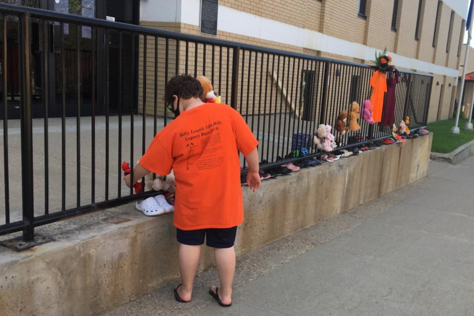 Grade 3 student Isaiah Bouchier placed shoes and a stuffed animal outside the Athabasca Provincial Building May 31 in memory of 215 Indigenous children whose unmarked graves were recently discovered at a former residential school in British Columbia. The impromptu memorial was shared on social media encouraging people to take shoes and other items down in the hope of having 215 items.