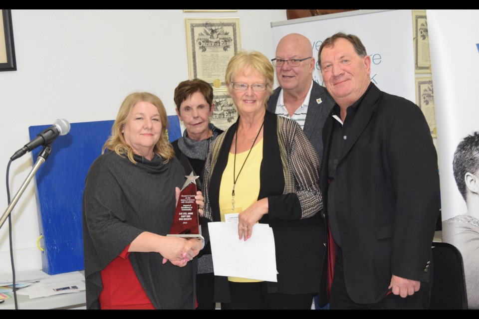 The Premier's Council on the Status of People with Disabilities member Cathy Smith presents the East Side Bus Society with the Excellence in Community award. L-R: East End Bus co-ordinator Lorna Porter, Summer Village of Sunset Point deputy mayor Ann Morrison, Smith, Alberta Beach Coun. Daryl Weber and Lac Ste Anne Coun. Lorne Olsvik. Barry Kerton/BL