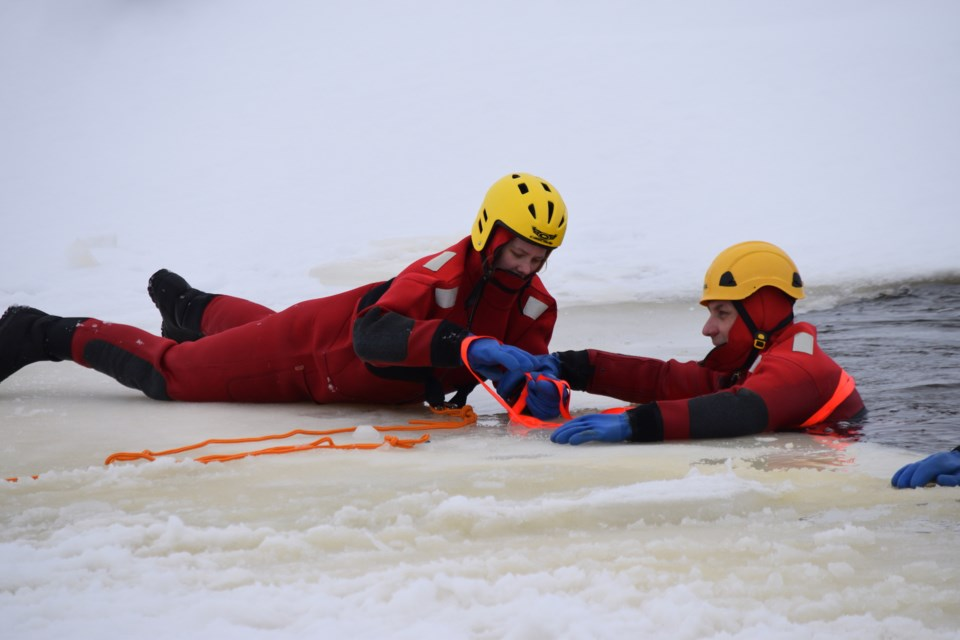 Barrhead firefighter Falon Arnott practices using a web-type strapping to rescue her colleague Jesse Whitney during a cold water exercise at the Barrhead reservoir. Barry Kerton/BL