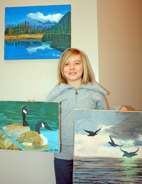 Rachelle Zadunayski shows off some of the artwork she will be auctioning off to help kids who have undergone brain surgery attend Camp He Ho Ha.