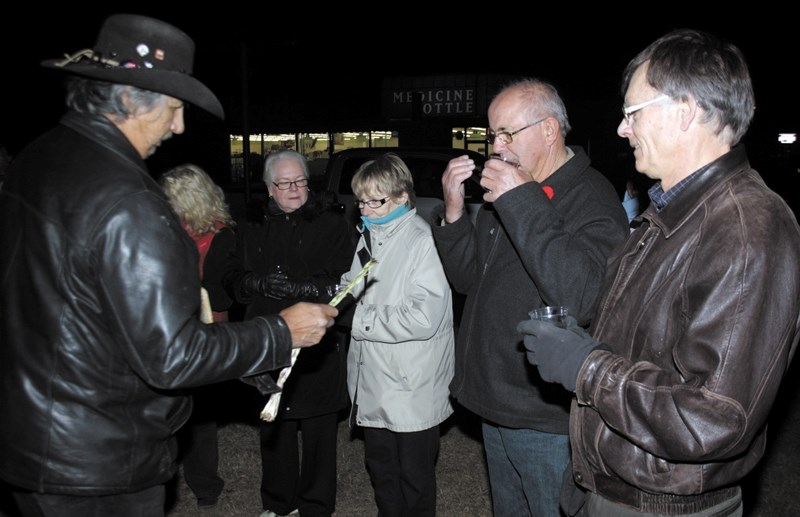 Woodlands Cree elder Alfred Beaver burned sweetgrass for participants of the candlelight vigil, including Westlock mayor Bruce Lennon (right) and Westlock County reeve