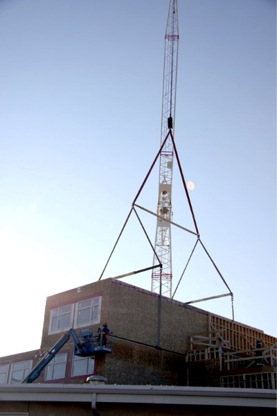 A crane lowers one of the Pembina Lodge housing modules into place. The expansion is on track and on budget.