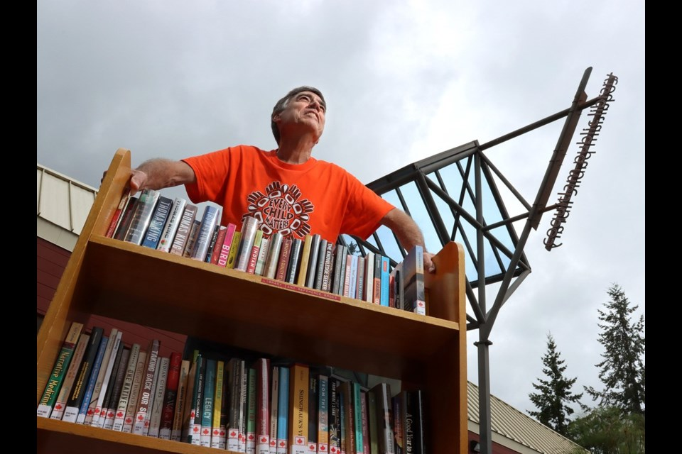 Coquitlam writer Alf Dumont, with some of his donated books at the Poirier library branch.