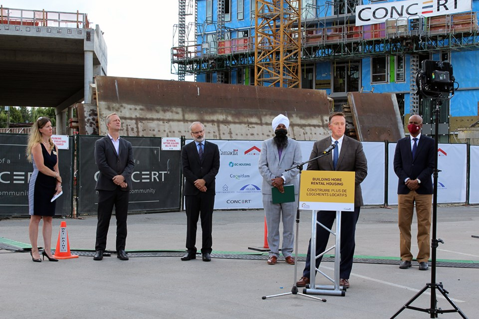 Left to right: Claire MacLean, CEO of SHARE Community Services Society/43 Housing; Rick Glumac, MLA for Port Moody-Coquitlam; Coquitlam Mayor Richard Stewart; Randeep Sarai, MP for Surrey Centre; Brian McCauley, president and CEO, Concert Properties (at podium); and Ahmed Hussen, Minister of Families, Children and Social Development and Minister Responsible for Canada Mortgage and Housing Corporation (CMHC).