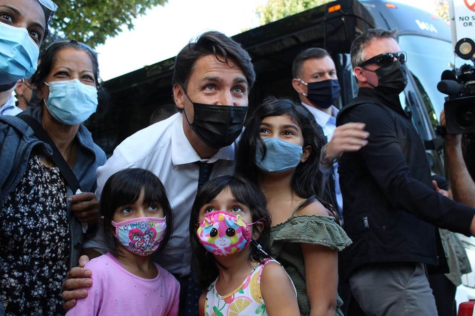 Justin Trudeau poses for a photo with a family in Port Coquitlam during Monday's stop.