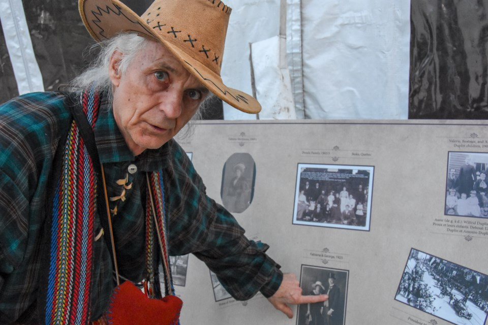 Roger Loubert at the 2019 Festival du Bois celebrations, pointing to photos of Maillardville pioneers.