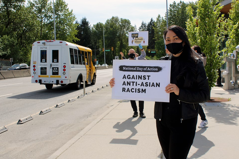Gina Chong of Port Moody holds a sign outside of the Inlet Centre SkyTrain station on the inaugural Day of Action.