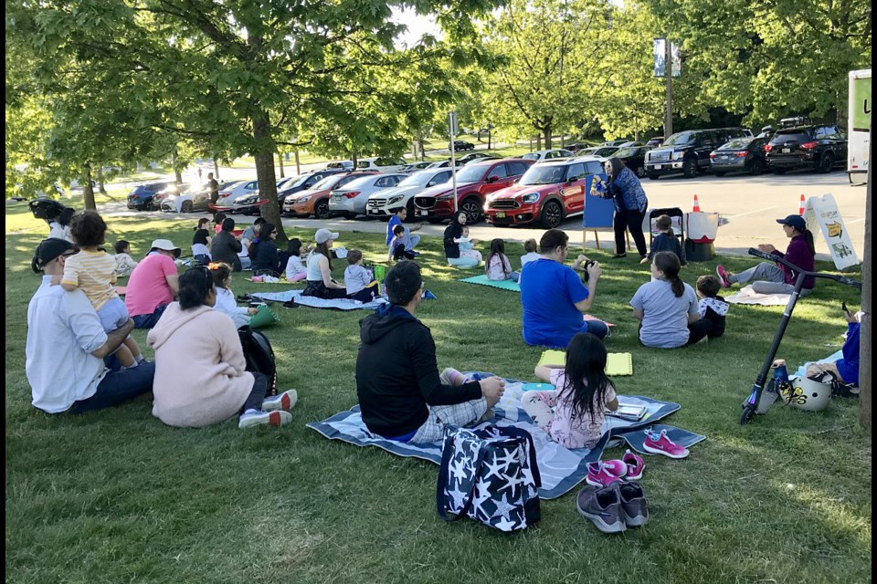 A program assistant with the Coquitlam Public Library reads a story to families at Town Centre Park in Coquitlam during a Library Link visit to the neighbourhood.