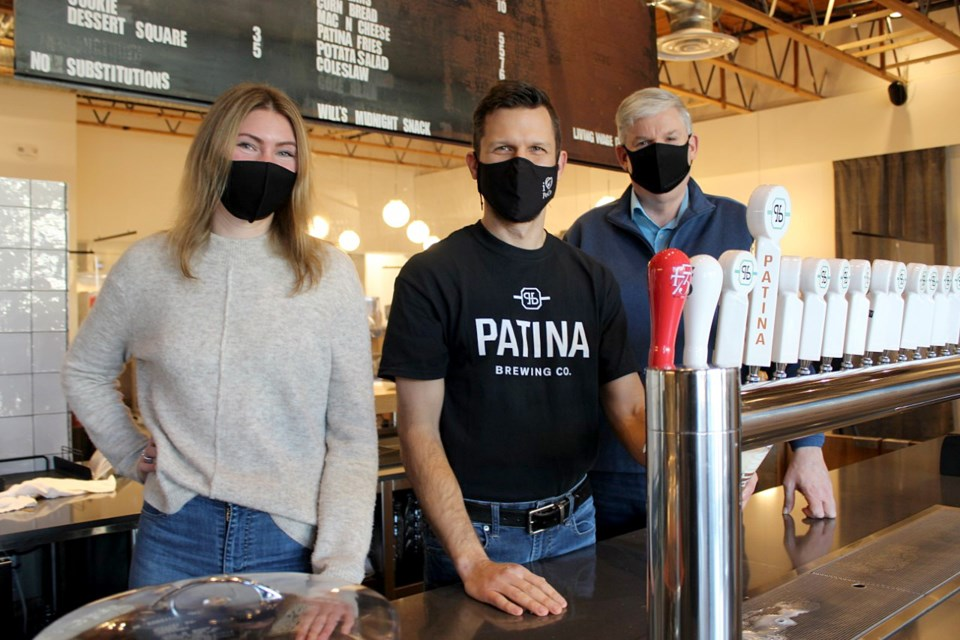 The Tri-CIties Chamber of Commerce's Stephanie Rennie and Michael Hind flank Kyle O'Genski, the CEO and a co-owner of Patina Brewing Co. — one of the 50 eateries taking part in the inaugural Taste of the Tri-Cities, from Feb. 15 to March 19.