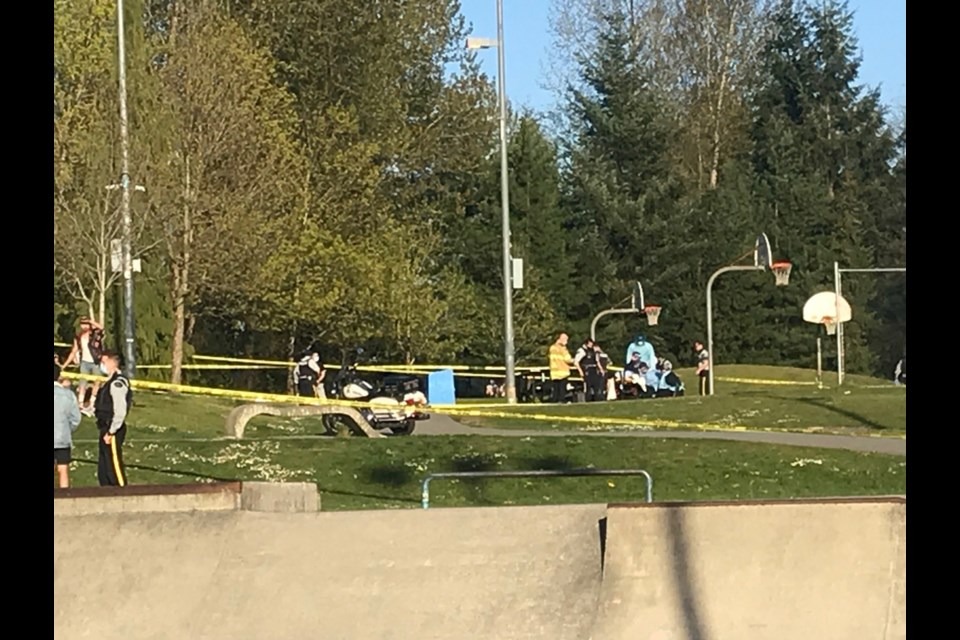 First responders work on the victim of an apparent shooting at the basketball courts at Coquitlam's Town Centre Park Monday evening.