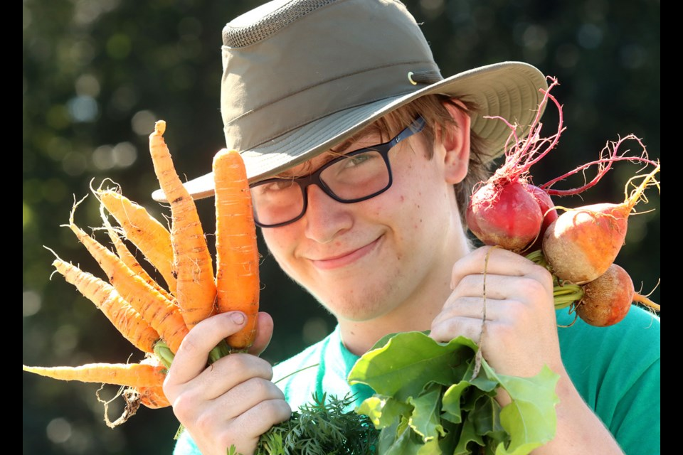 Showing off a colourful carrot and beet crop is Jack Elliot, a Coquitlam student selling veggies at a Fresh Roots pop up stand.