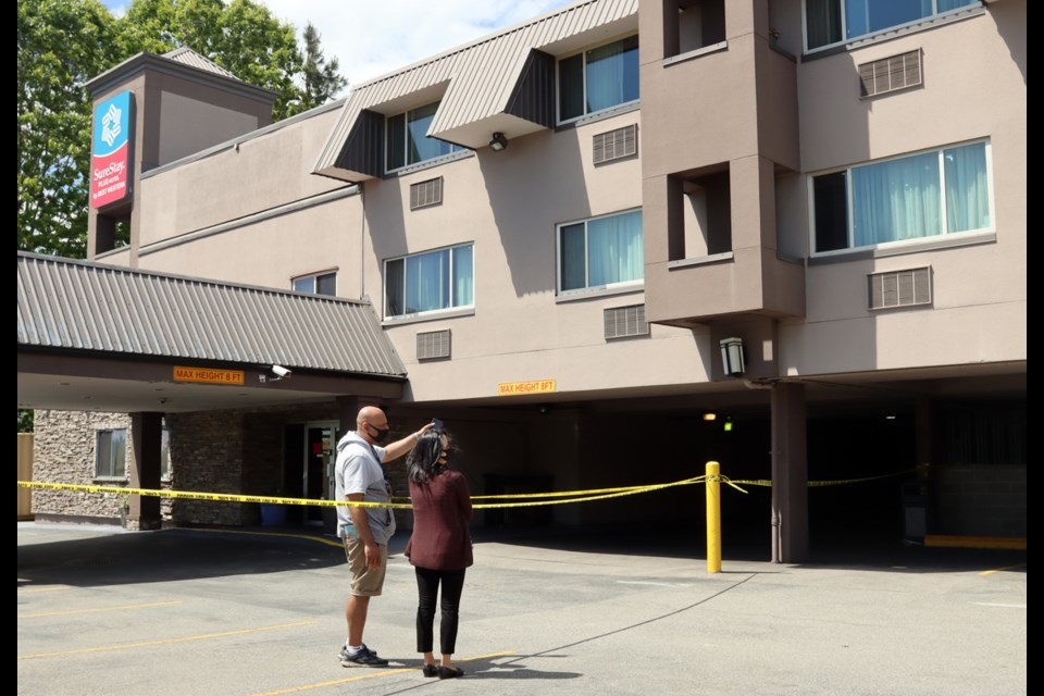 Staff survey the damage to the Sure Stay hotel on Brunette Avenue in Coquitlam after a fire Wednesday destroyed at least one room.
