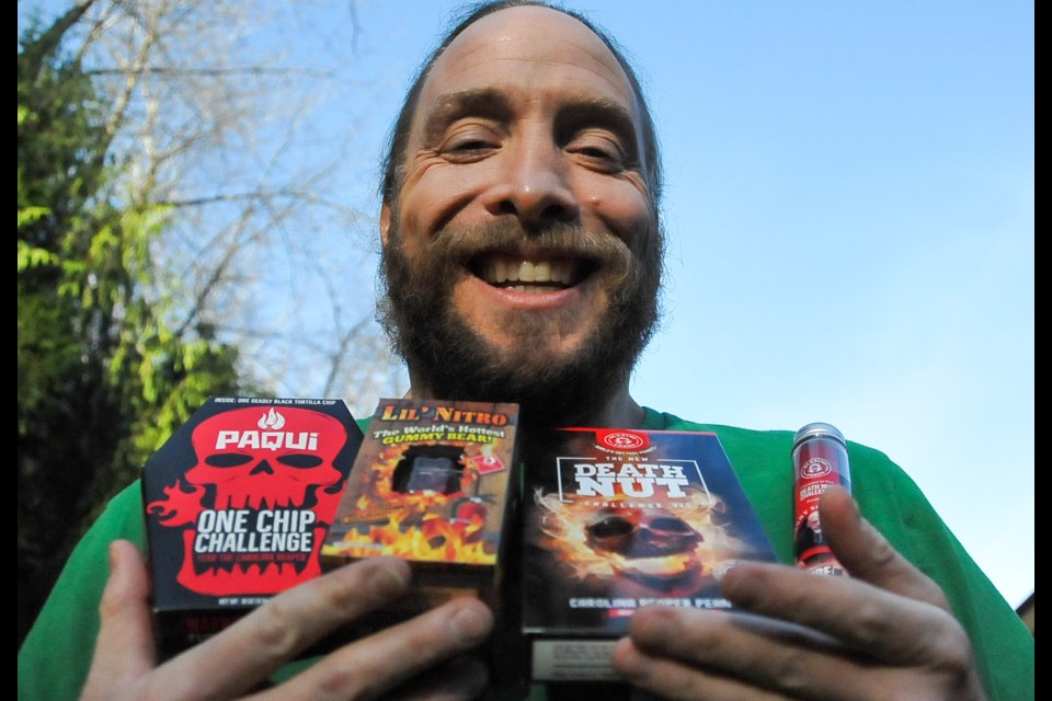 "Dave McCloskey displays a menu of spicy edibles, from Paqui's One Chip Challenge and Lil Nitro gummy bear — the ""world's spiciest"" — to Death Nut and the Tube of Terror. They are all part of a live-streamed challenge aimed at raising money for the Tri-Cities food bank. - Photograph by STEFAN LABBÉ/TRI-CITY NEWS"