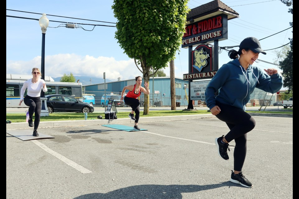 Lalaine Baldovi leads a fitness class in the front parking lot at the Cat & Fiddle pub in Port Coquitlam.