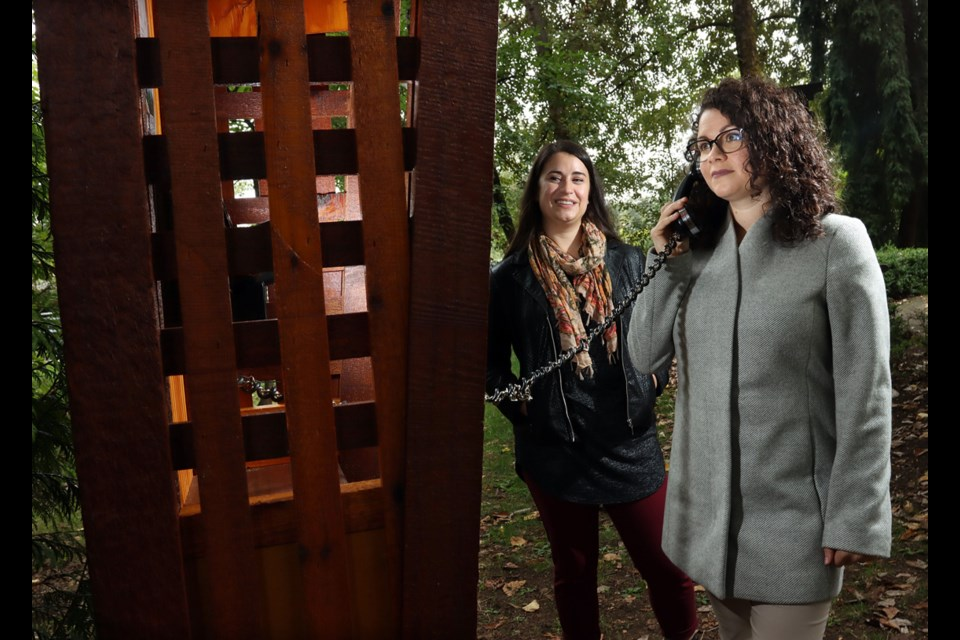 """Amelie Lambert and Brittany Borean, of Crossroads Hospice, place a call from the new phone of the wind that's been installed in Port Moody's Pioneer Park to allow grieving family members to place a """"call"""" to their departed loved ones."""