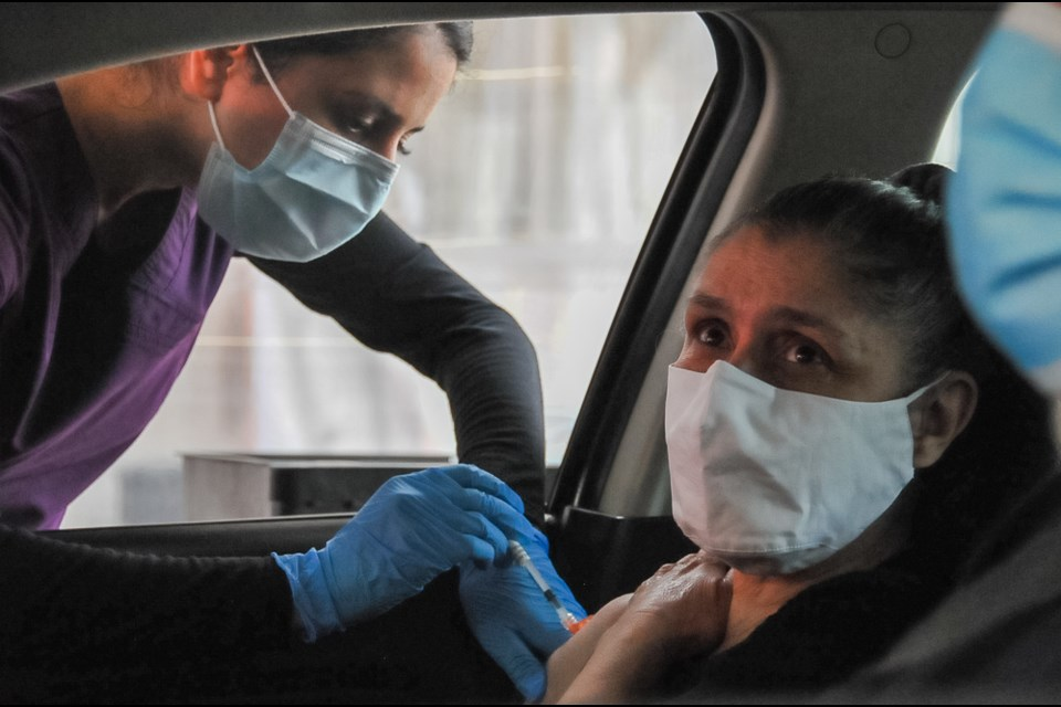 Maria Yule of Port Coquitlam receives a COVID-19 vaccine at the Coquitlam drive-thru testing and vaccination centre. May 5, 2021.