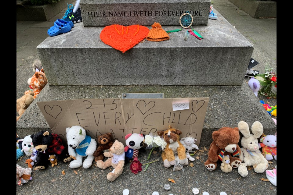 Tributes, including shoes and teddy bears, are being placed at the Port Coquitlam cenotaph in the wake of news that the bodies of 215 children have been discovered outside of a former Kamloops residential school.