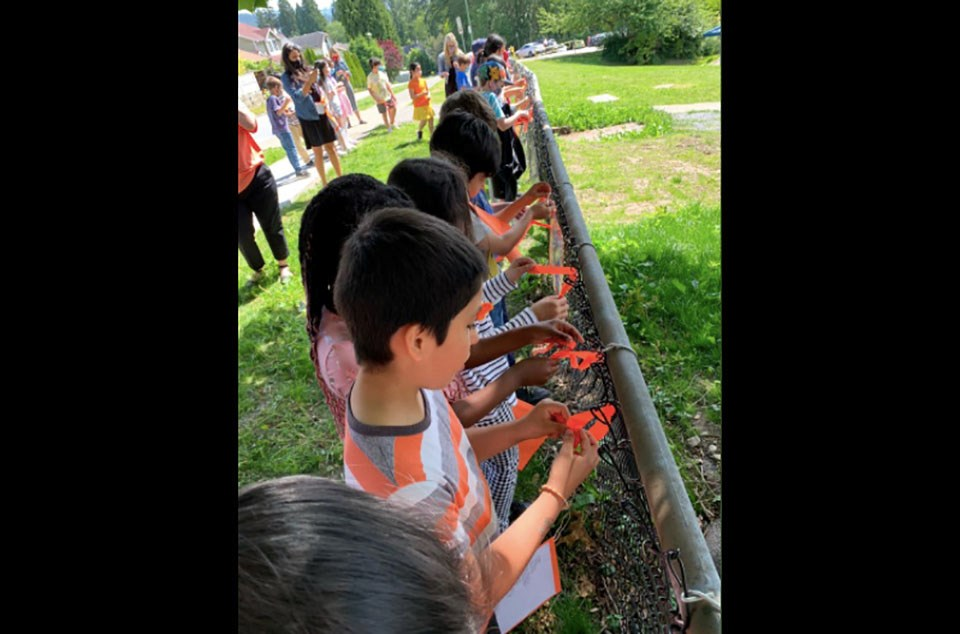 Children tie orange ribbons onto a fence outside Walton Elementary in Coquitlam.